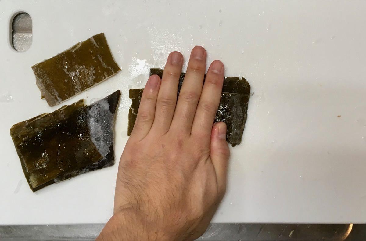 冷凍した昆布のだしがらは押しつぶすことで切りやすくなる